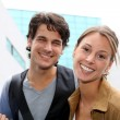 Cheerful couple of students standing on college campus — Stock Photo #13965476