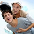 Stock Photo: Man giving piggyback ride to girlfriend