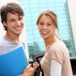 Cheerful couple of students standing on college campus — Stock Photo #13965502