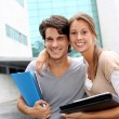 Cheerful couple of students standing on college campus — Stock Photo #13965503