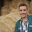 Portrait of cheerful farmer standing in front of hay rolls — Stock Photo