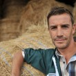 Portrait of cheerful farmer standing in front of hay rolls — Stock Photo #13965532