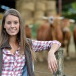 Stock Photo: Smiling farmer womstanding by cattle outside