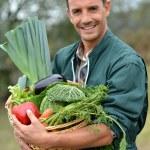 Portrait of smiling farmer holding vegetables basket — Stock Photo