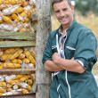 Cheerful farmer standing by corn silo — Stock Photo
