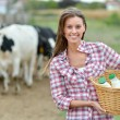 Stock Photo: Smiling young farmer carrying bottles of fresh milk