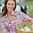 Smiling young farmer carrying bottles of fresh milk — Stock Photo #13965637