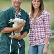 Smiling couple of duck breeders standing outdoors — Stock Photo