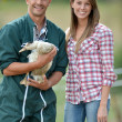 Stock Photo: Smiling couple of duck breeders standing outdoors