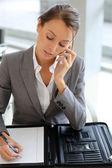 ノートを取る電話で通話しているビジネスの少女 — ストック写真