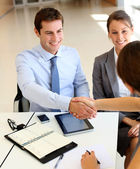 Business associates shaking hands in office — Stok fotoğraf