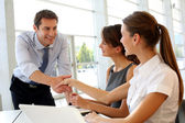 Salesman shaking hands to clients — Stock fotografie