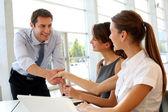 Verkoper schudden handen aan klanten — Stockfoto