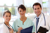 Smiling medical team standing in hall — Stock Photo