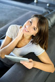 Attractive woman sitting in couch with electronic tablet — Stock Photo