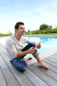 Man sitting by pool with digital tablet — Stock Photo
