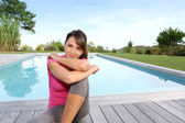 Woman sitting by pool after exercising — Stock Photo