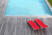 View of red long chairs set by swimming-pool — Foto de Stock