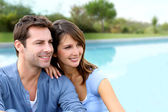 Cheerful couple sitting in front of new house — Stock Photo