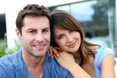 Cheerful couple sitting in front of new house — Stock fotografie