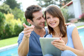 Couple websurfing on internet with tablet — Stock Photo