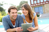 Couple websurfing on internet with tablet — Stok fotoğraf