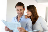 Couple reading news on newspaper and internet — Stock Photo