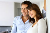 Smiling couple looking away by window — Stock Photo