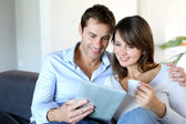 Couple in sofa websurfing on internet with tablet — Stock Photo