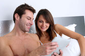 Couple in bed websurfing on internet — Stock Photo