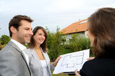Couple meeting saleswoman on construction site — Stockfoto