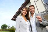 Pareja frente a su casa nueva con llaves de la puerta — Foto de Stock