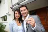 Couple in front of new home holding door keys — Foto Stock
