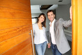 Couple opening the front door of their home — Foto Stock