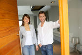 Couple opening the front door of their home — Stock Photo