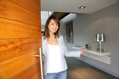 Woman opening her house door to welcome — Stockfoto