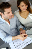 Couple at home looking at future home blueprint — Stock Photo