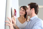Couple choosing paperwall colour for their new home — Stock Photo