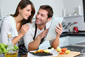 Couple in home kitchen using electronic tablet — ストック写真