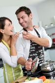 Man preparing dinner and making her wife taste the food — Stock Photo