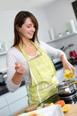 Woman in kitchen preparing pasta dish — Stok fotoğraf