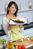 Woman in kitchen holding fish dish — Stock Photo