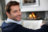 Man at home reading newspaper in front of fireplace — Stock Photo