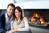 Romantic couple sitting by fireplace at home — Stock Photo