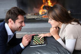 Couple sitting by fireplace and websurfing with tablet — Stock Photo