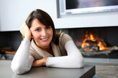 Beautiful woman sitting by fireplace at home — Stock Photo