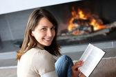 Portrait of beautiful woman reading book by fireplace — Foto de Stock