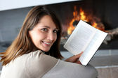 Portrait of beautiful woman reading book by fireplace — Stock Photo