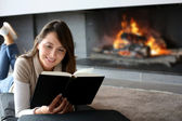 Portrait of beautiful woman reading book by fireplace — Stock fotografie