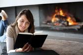 Portret pięknej kobiety czytając książkę przy kominku — Zdjęcie stockowe